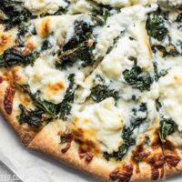 Garlicky greens and creamy ricotta pair perfectly on this light and fresh Garlicky Kale and Ricotta Pizza. It's the perfect pizza for summer! BudgetBytes.com