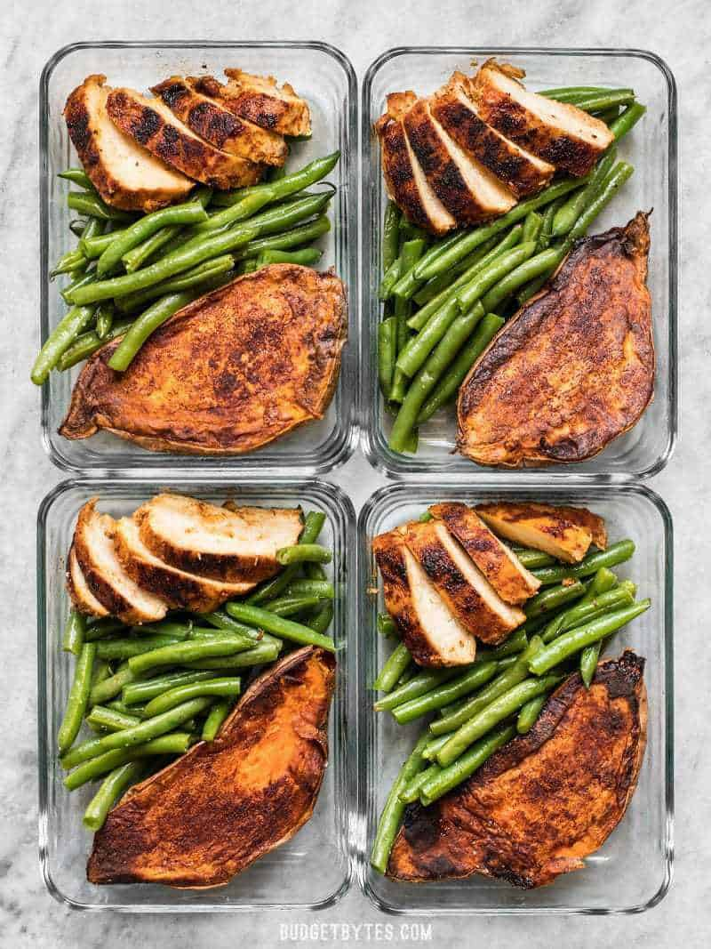 Four glass meal prep containers with Smoky Chicken and Cinnamon Roasted Sweet Potatoes