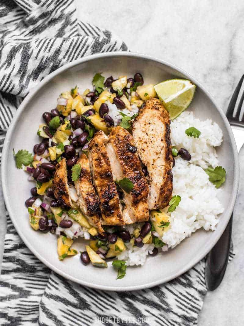 Sliced Jerk Chicken on a bed of rice with Pineapple Black Bean Salsa, limes, and cilantro