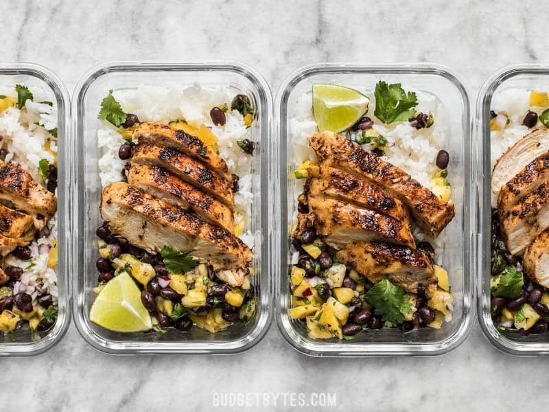 Glass meal prep containers with Jerk Chicken and Pineapple Black Bean Salsa lined up in a row.