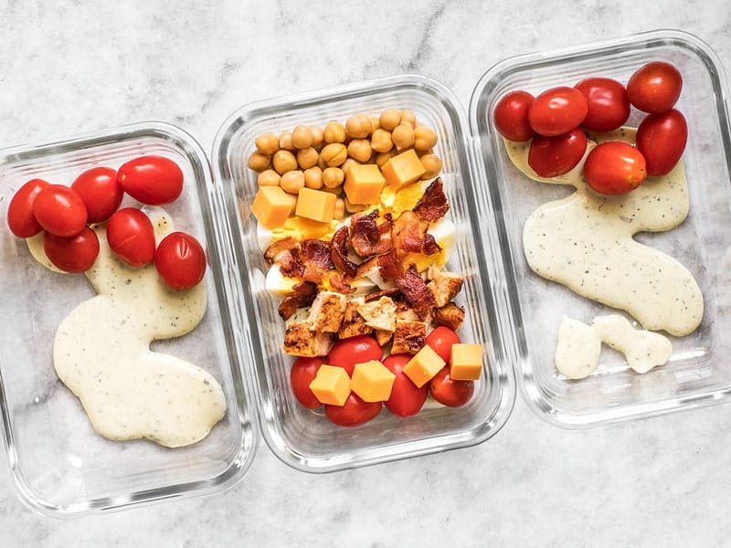 Add dressing tomatoes cheese bacon and beans to meal prep containers
