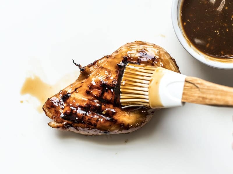 Teriyaki Sauce being brushed onto a grilled chicken breast