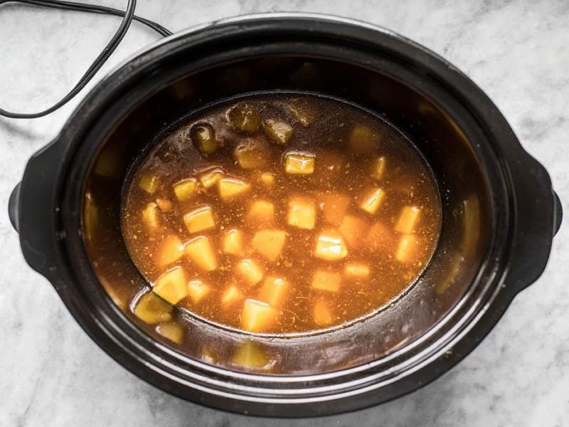 Thickened pineapple teriyaki chicken sauce with pineapple chunks in slow cooker