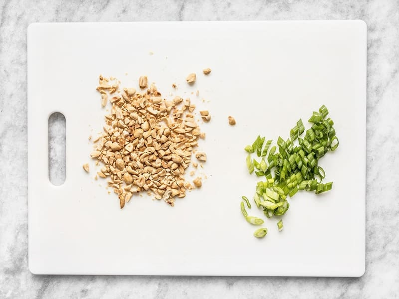 Chopped Peanuts and Sliced Green Onion on a cutting board