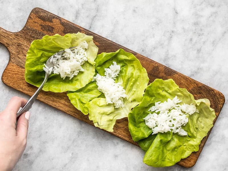 Rice being added to lettuce leaves on a wooden cutting board