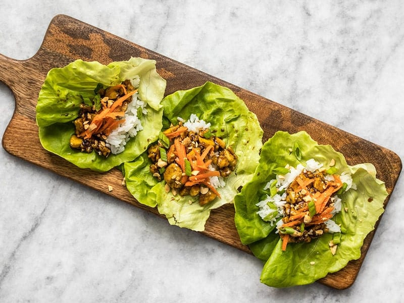 Hoisin Tofu added to lettuce cups with shredded carrot peanuts and green onion