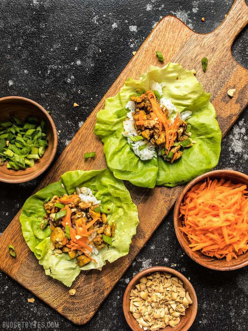 Two Hoisin Tofu Lettuce Cups on a wooden cutting board with bowls of toppings on the sides