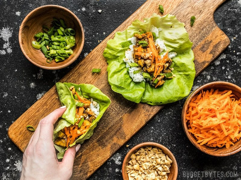A hand taking one Hoisin Tofu Lettuce Cup from a wooden cutting board with toppings nearby