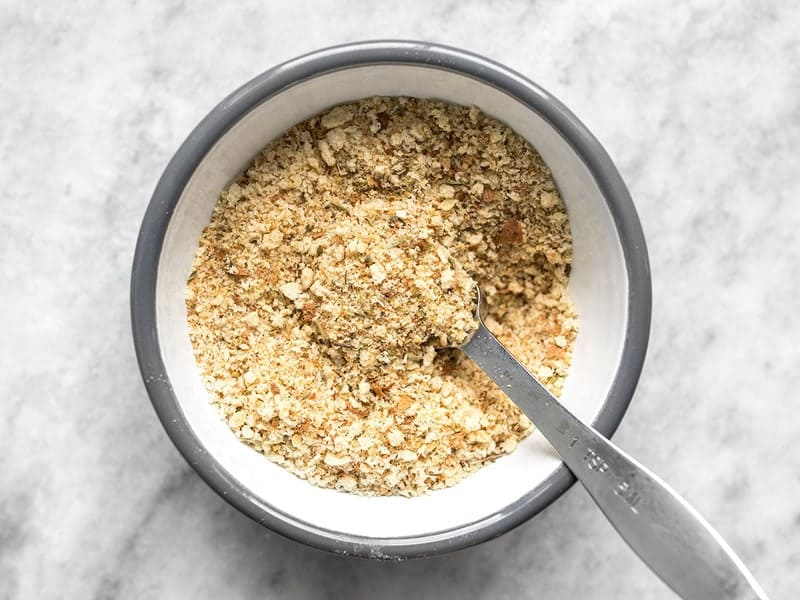 Finished Italian flavored breadcrumbs in a bowl with a measuring spoon