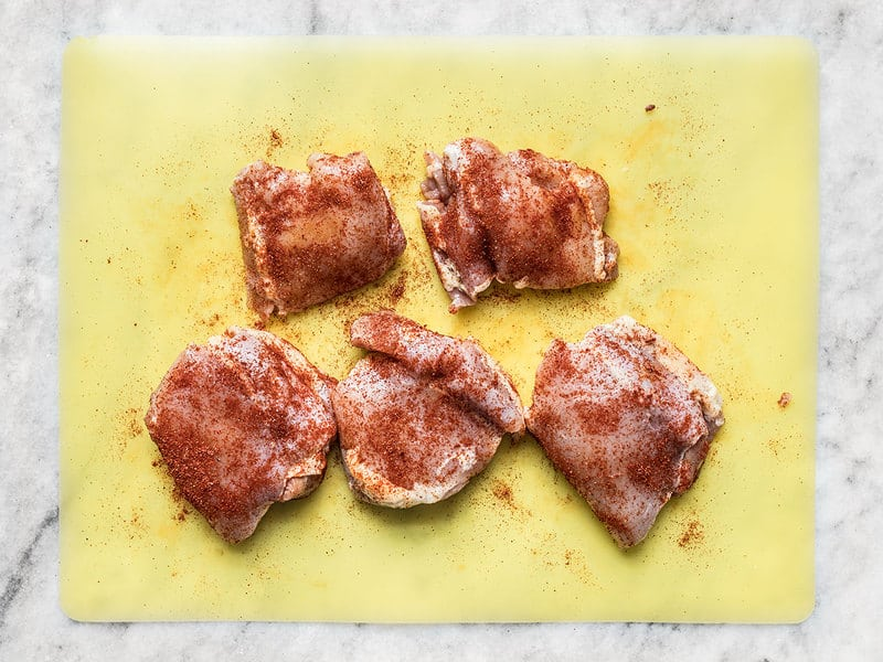 Seasoned Chicken Thighs on a cutting board