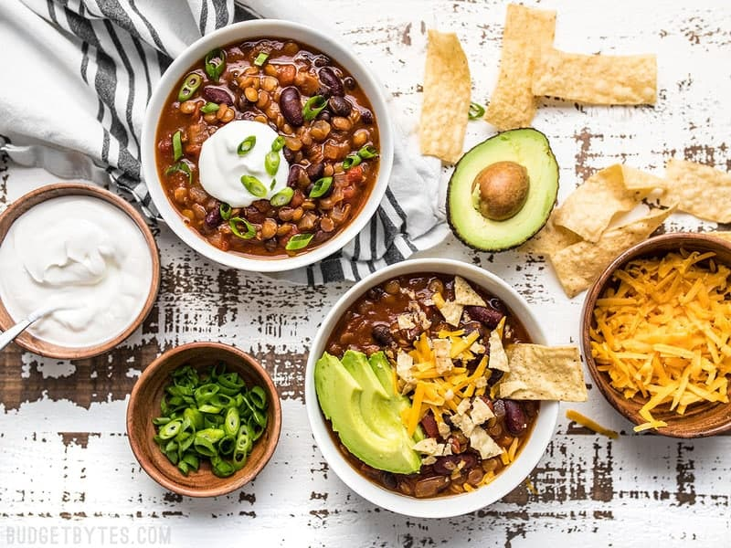 Dressed bowls of Slow Cooker Vegetarian Lentil Chili with various toppings on the side