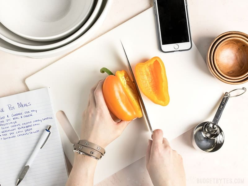 Hands cutting a yellow bell pepper with notes, bowls, measuring spoons, and a phone near by.