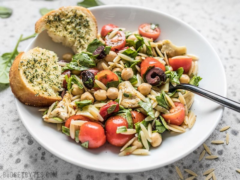 Front view of Italian Orzo Salad with a piece of garlic bread.