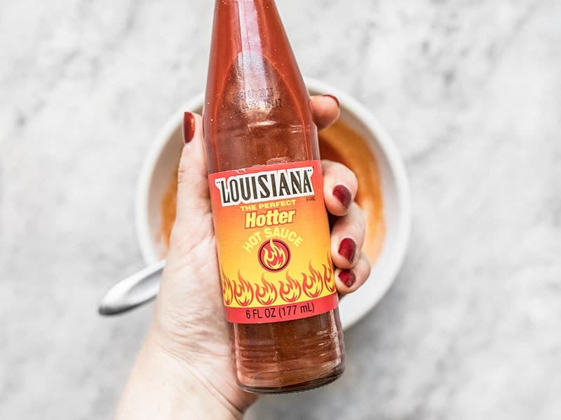 Louisiana Hot Sauce bottle being held over a bowl