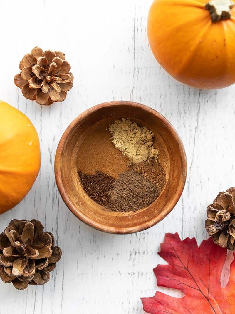 A small wooden bowl with spices, surrounded by pinecones, pumpkins, and leaves
