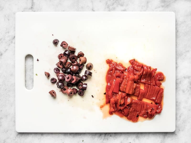 Chopped kalamata olives and roasted red peppers on the cutting board