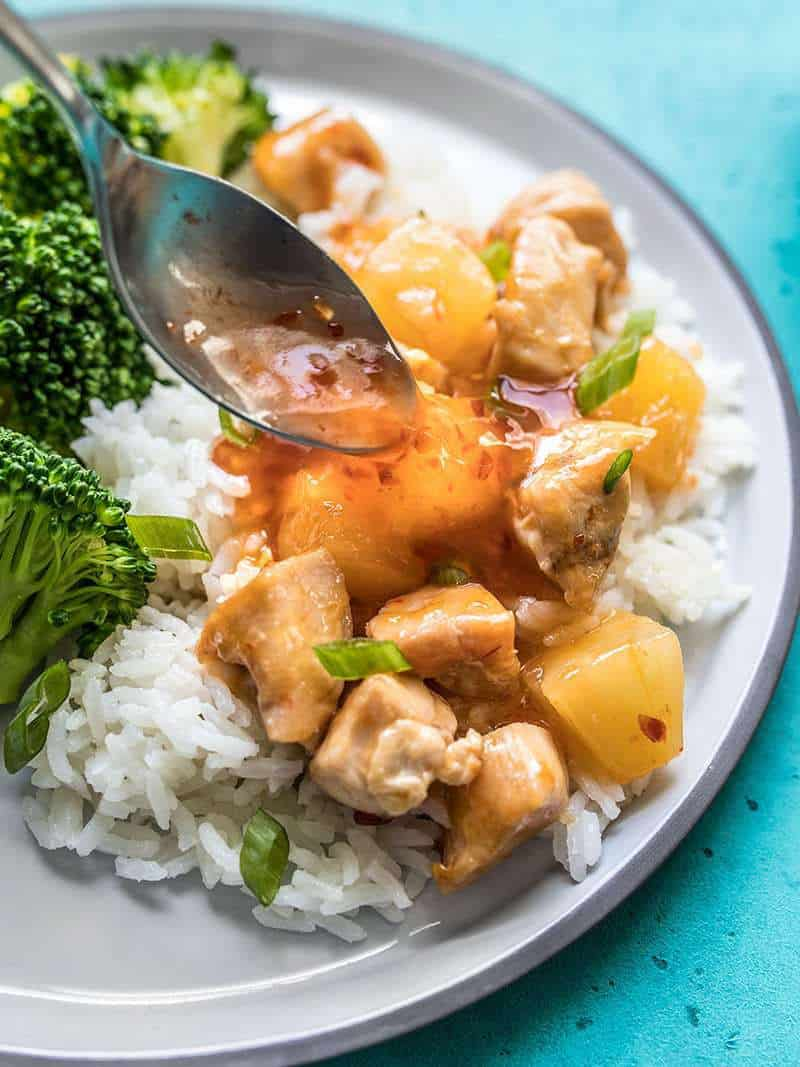 Sweet Chili Sauce being spooned onto a plate of chicken stir fry with broccoli and rice