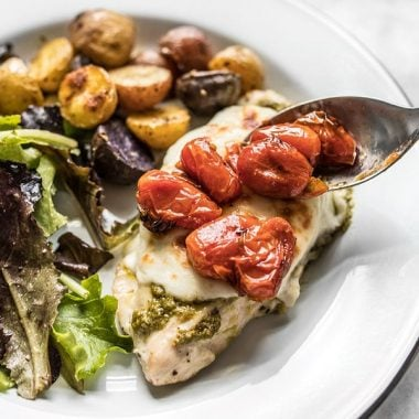 Close up of roasted tomatoes on top of Sheet Pan Pesto Chicken DInner