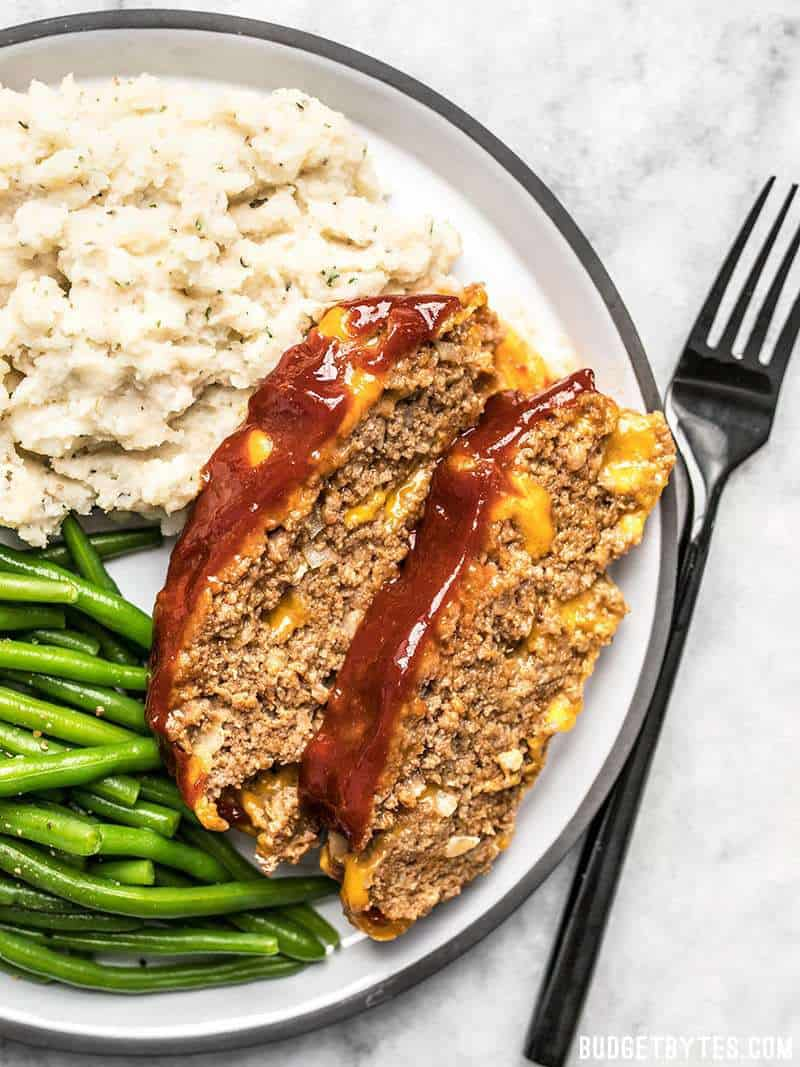Two Slices of Cheddar Cheeseburger Meatloaf with mashed potatoes and green beans.