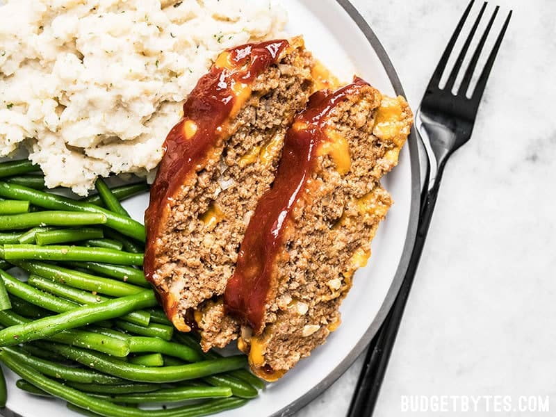 Two slices of Cheddar Cheeseburger Meatloaf on a dinner plate with mashed potatoes and green beans
