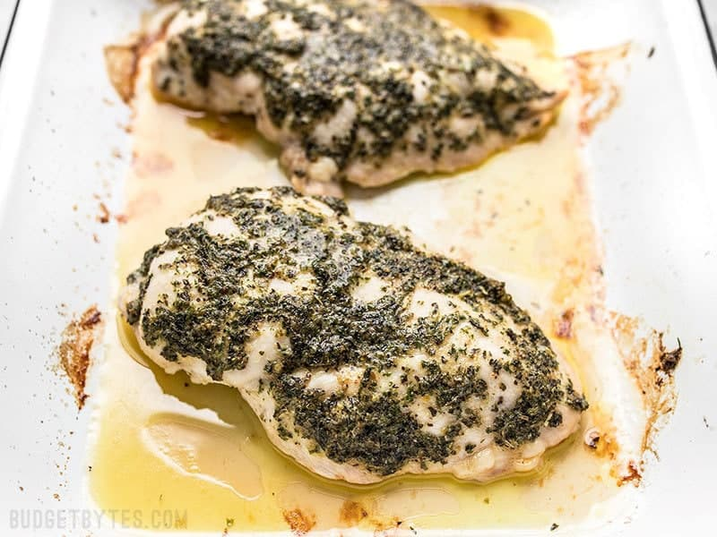Garlic Herb Baked Chicken Breast in baking dish with juices.