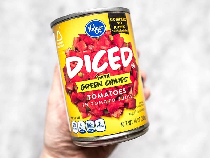 A can of diced tomatoes with green chiles being held in a hand