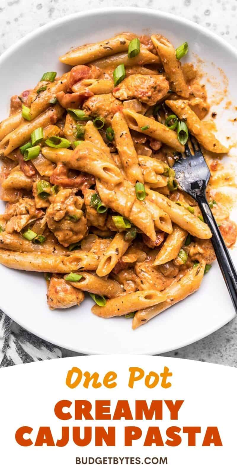 Close up of a bowl of creamy cajun chicken pasta, title text at the bottom