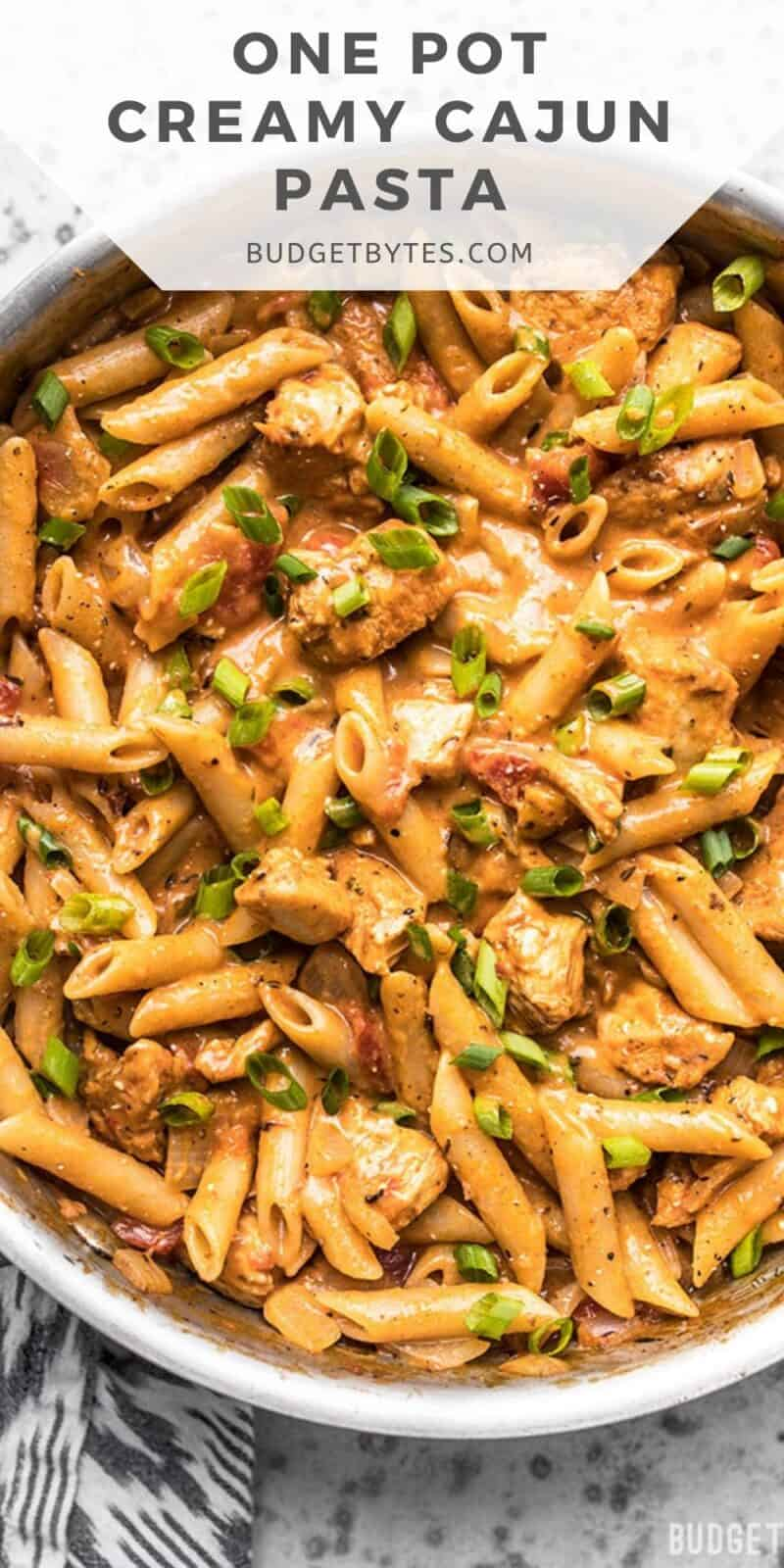 Overhead view of cajun chicken pasta in the skillet, title text at the top