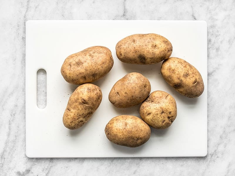 Seven Russet Potatoes on a white cutting board