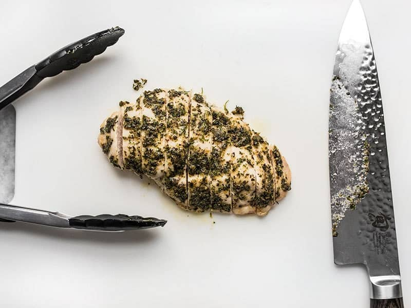 Sliced garlic herb chicken breast on a cutting board with tongs and a knife