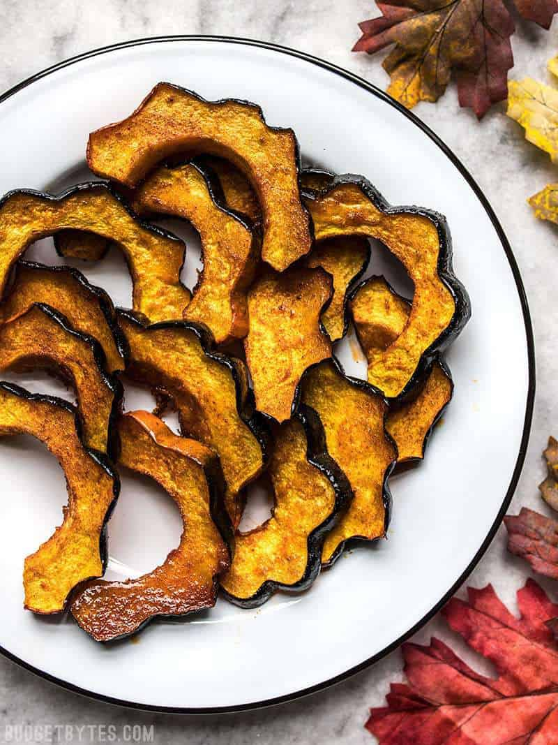 A plate full of Smoky Maple Roasted Acorn Squash on a holiday table.