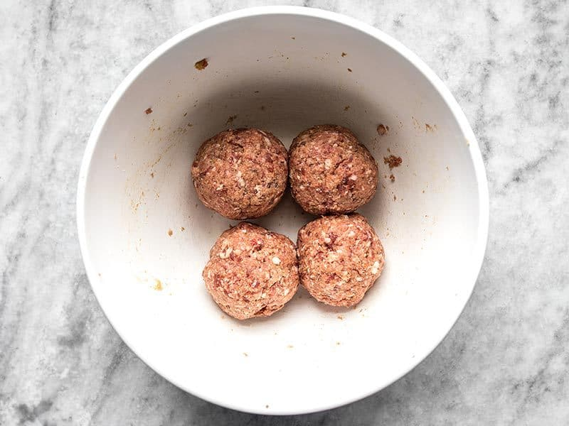 Shaped uncooked meatballs in a white bowl