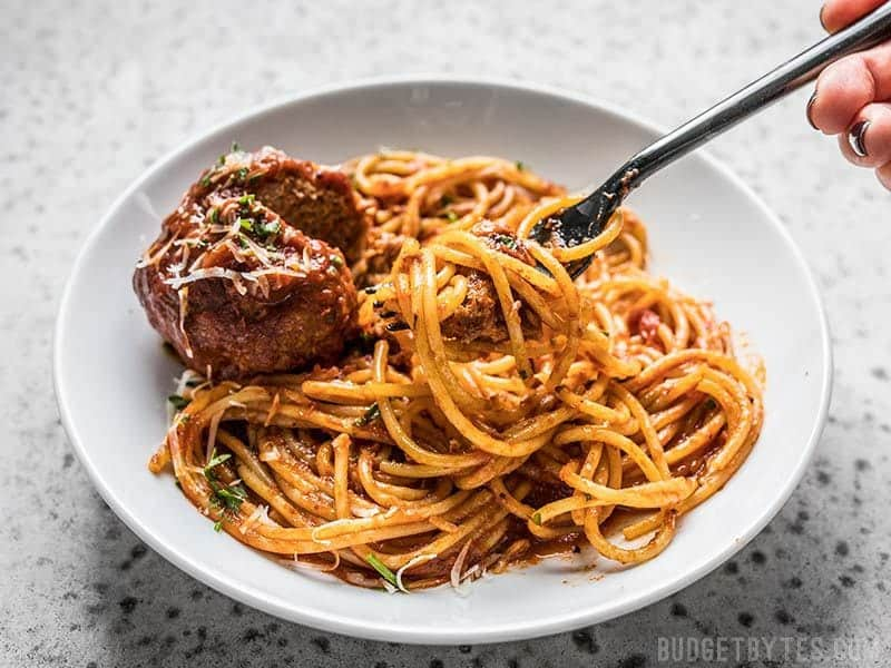 A fork twirled with spaghetti and marinara on a plate with a Giant Slow Cooker Meatball
