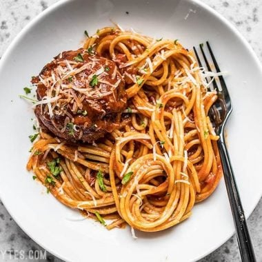 A plate with spaghetti, marinara, and a giant slow cooker meatball.