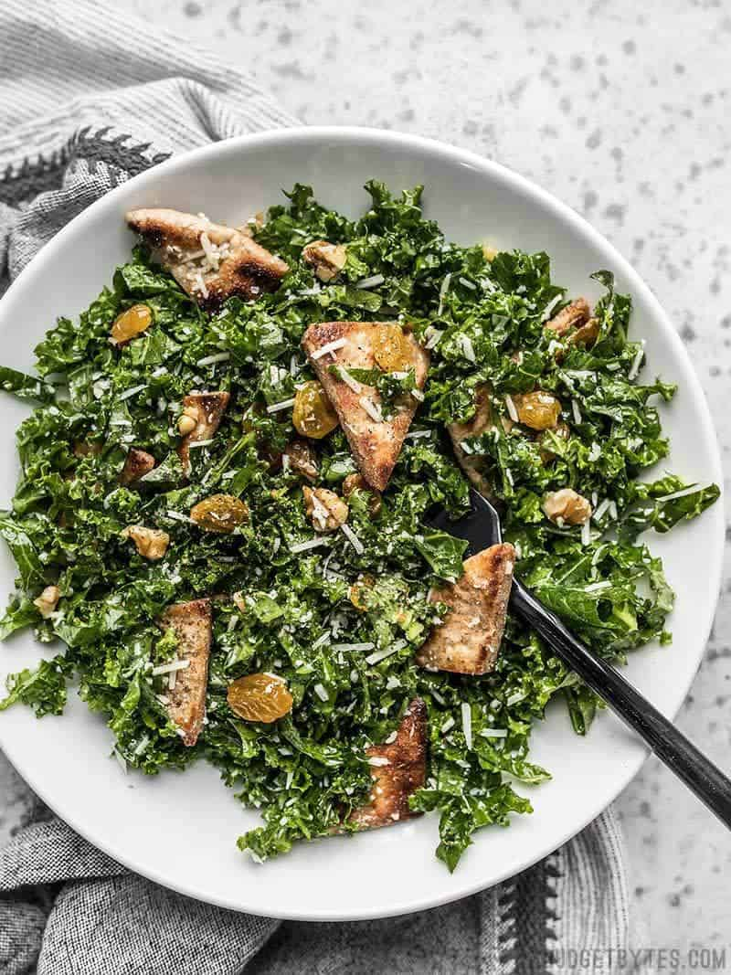 A big bowl full of Kale Salad with Toasted Pita, Parmesan, Walnuts, and Golden Raisins.