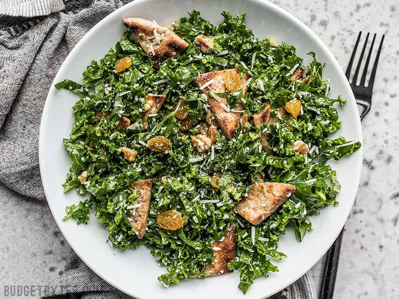 A plate full of Kale Salad with Toasted Pita, Parmesan, Walnuts, and Golden Raisins