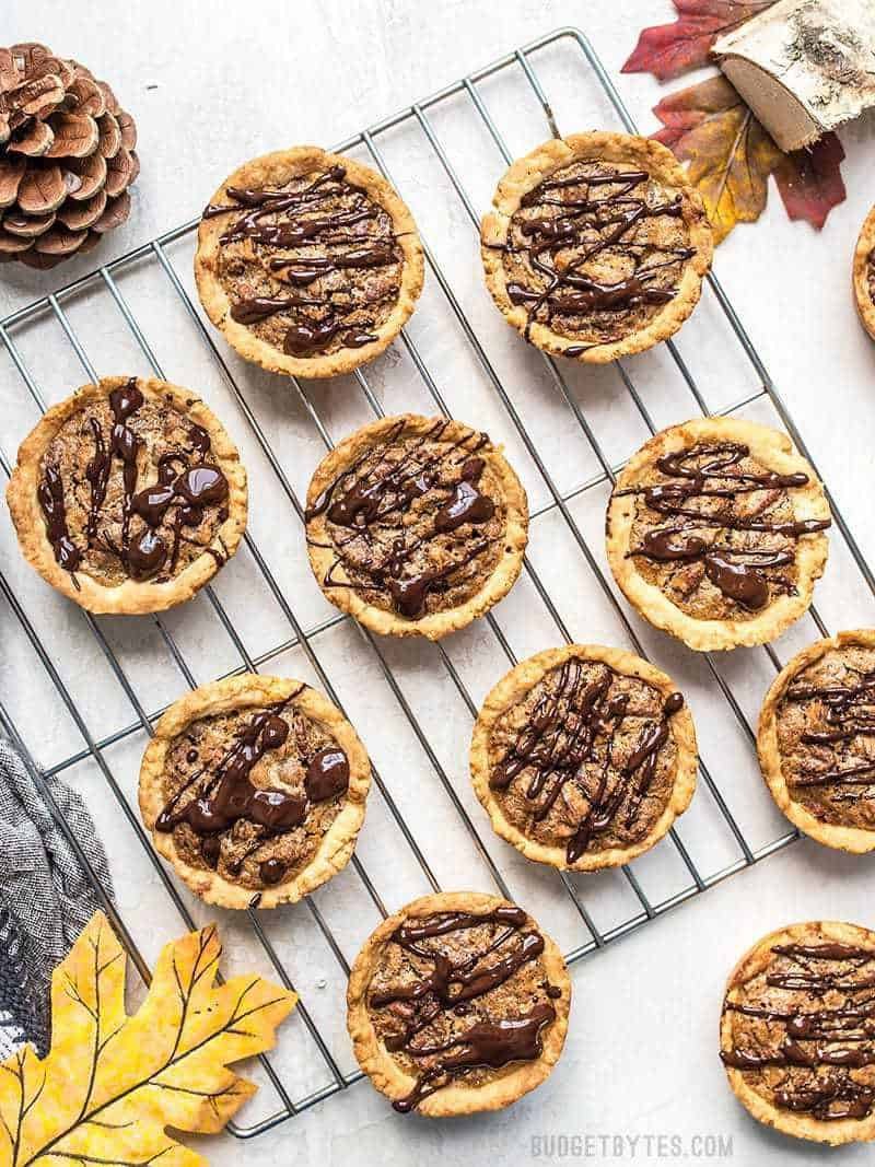 Mini Dark Chocolate Pecan Pies on a cooling rack ready to eat.