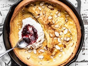 Close up of jam being spread on ricotta inside a baked Almond Dutch Baby
