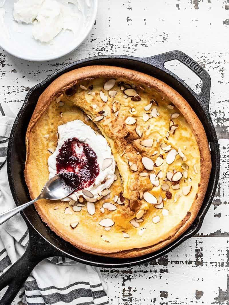 An Almond Dutch Baby with Ricotta and Jam in a cast iron skillet ready to slice and serve.