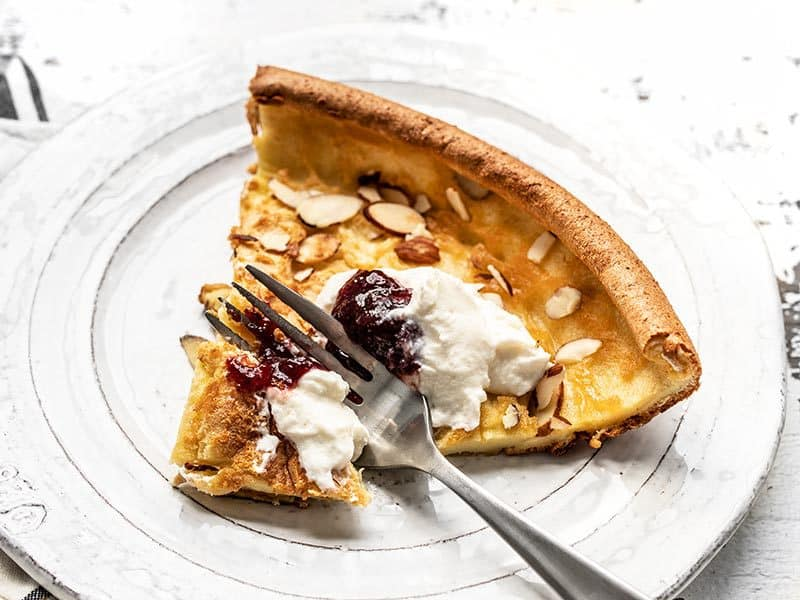 One slice of Almond Dutch Baby with Ricotta and Jam being eaten.