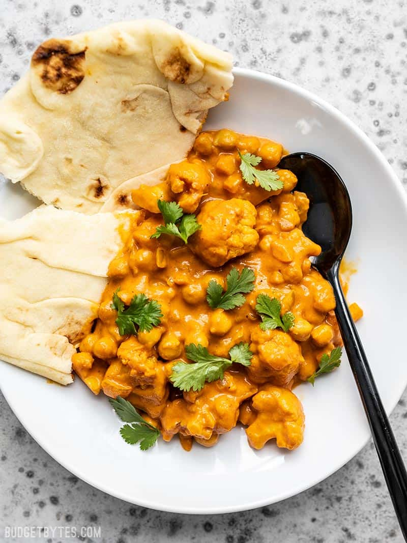A bowl full of Cauliflower and Chickpea Masala with a black spoon and torn piece of naan bread.