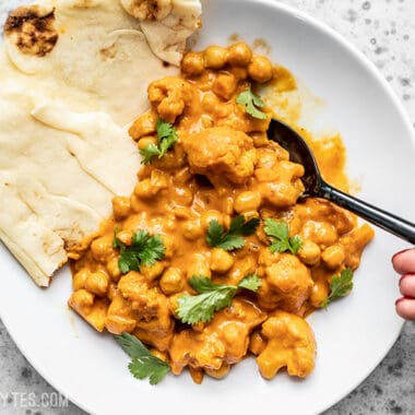 A bowl of creamy Cauliflower and Chickpea Masala being eaten with a spoon and two pieces of naan on the side.