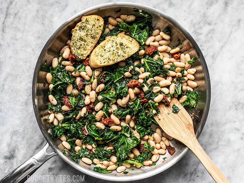 Finished Sun Dried Tomato, Kale, and White Bean Skillet with wooden spatula