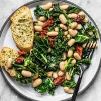 A plate full of Sun Dried Tomato, Kale, and White Bean Skillet with garlic bread
