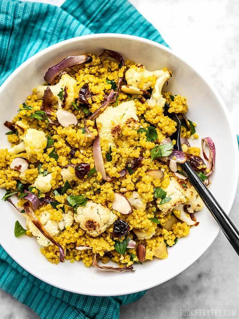 A bowl full of Roasted Cauliflower and Quinoa Salad on a teal napkin.