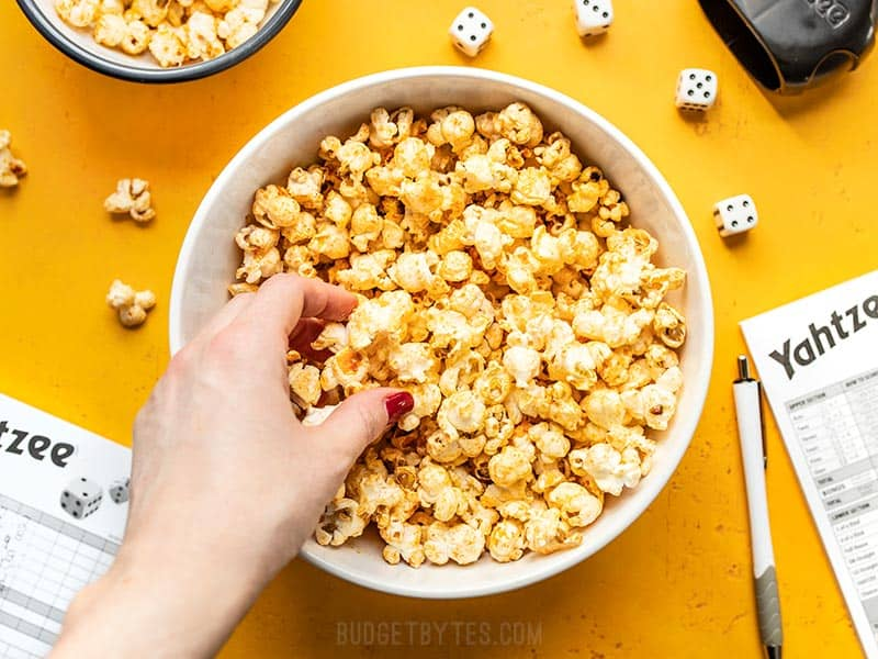 A hand grabbing some Sriracha Nooch Popcorn out of a large bowl on a yellow background.