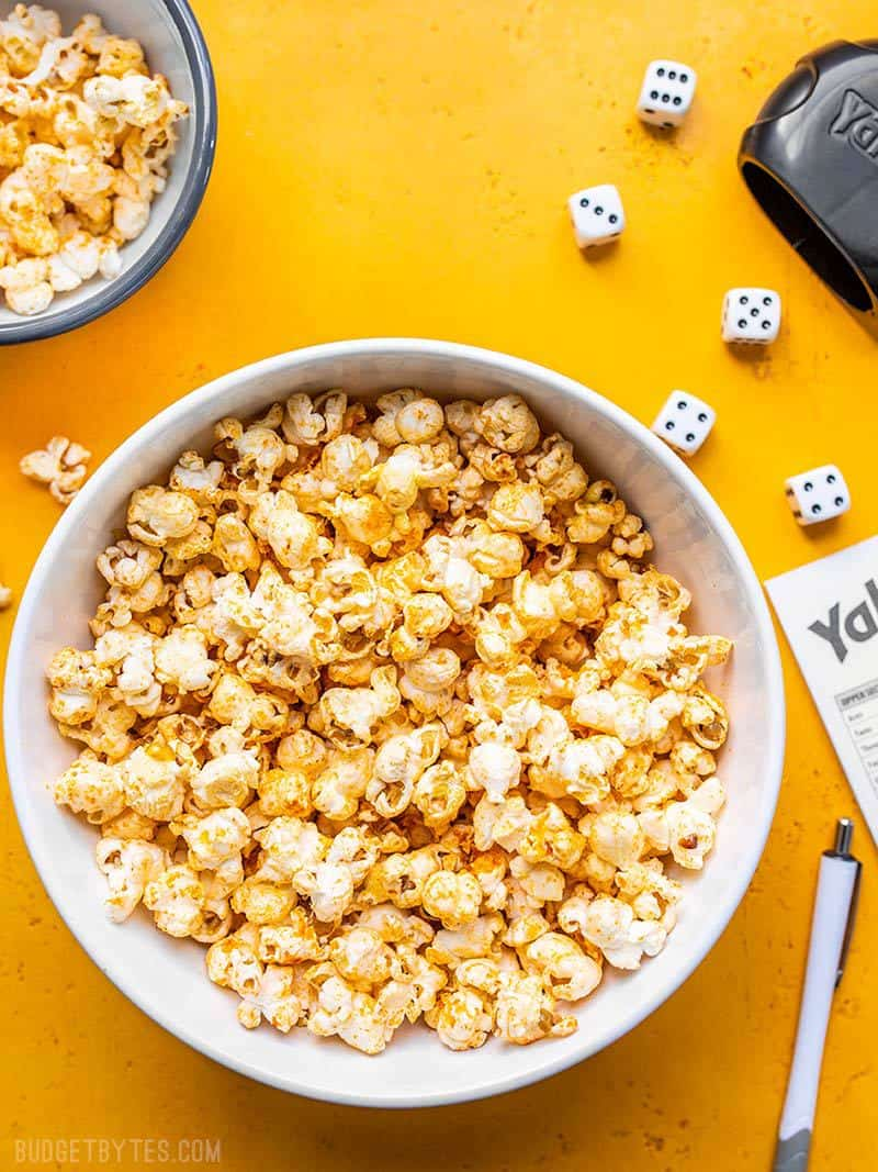 Sriracha Nooch Popcorn in a white bowl on a yellow background surrounded by dice