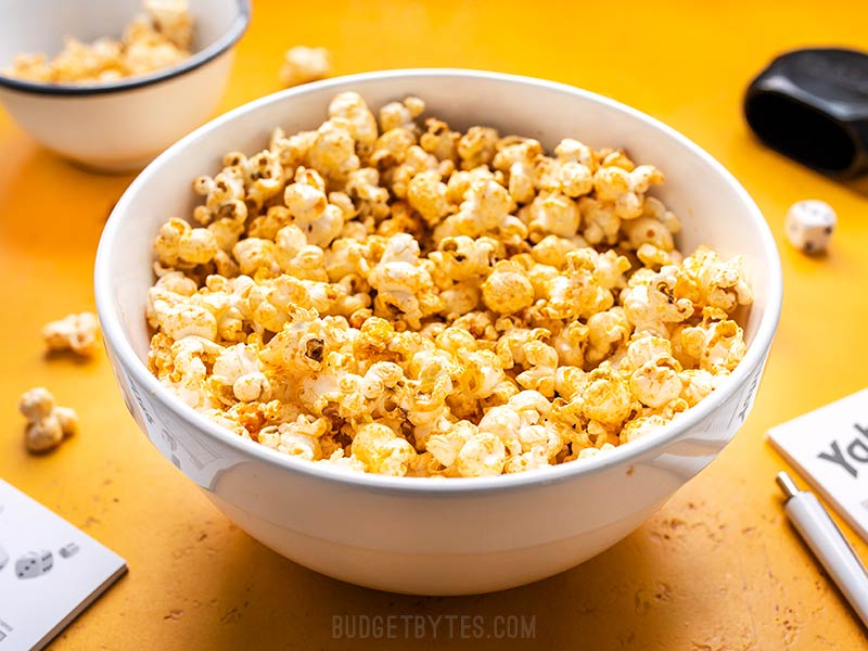 Front view of a bowl of Sriracha Nooch Popcorn on a yellow background.