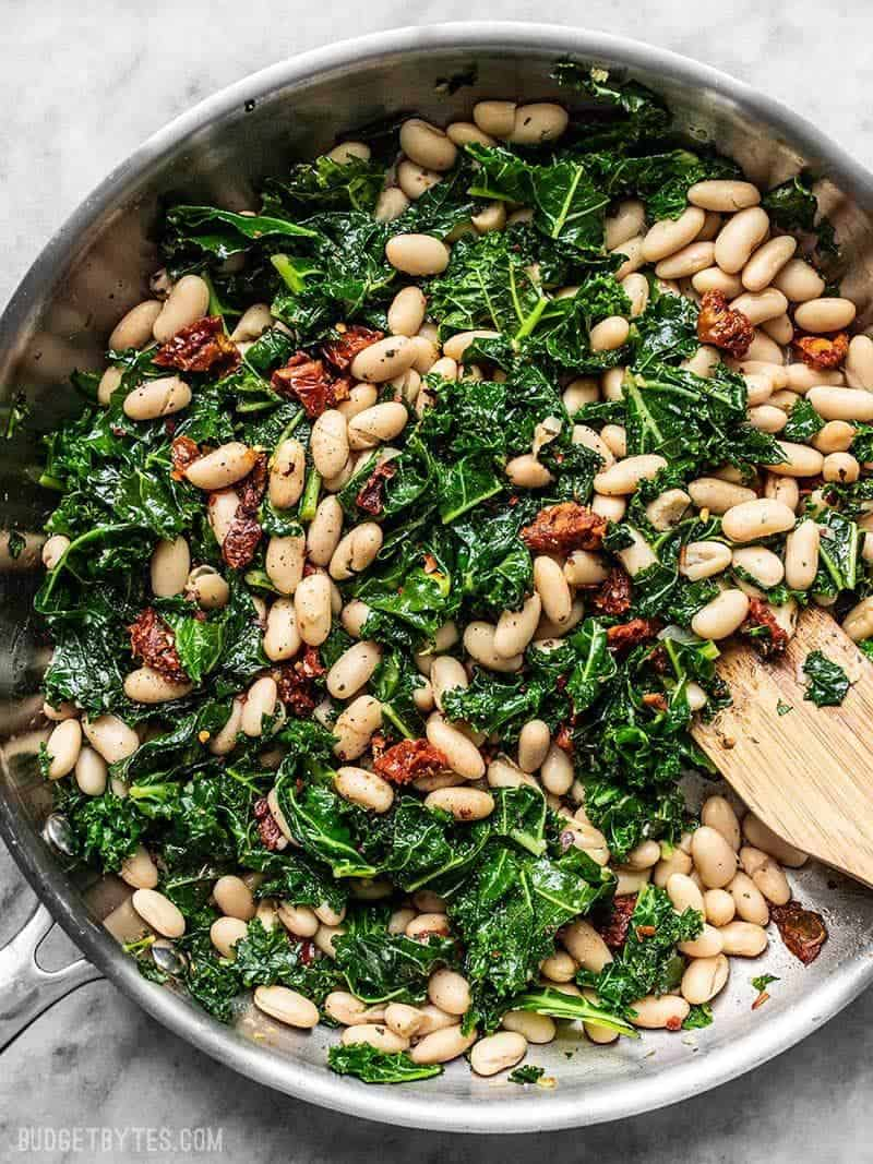 A skillet full of Sun Dried Tomato, Kale, and White Beans, with a wooden spatula.
