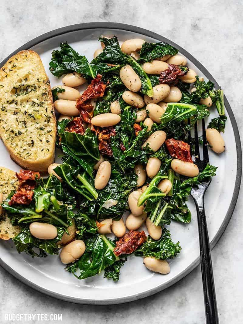 Close up of a plate full of Sun Dried Tomato, Kale, and white Bean Skillet with Garlic Bread